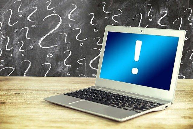 Imagem de computador com um ponto de exclamação em frente a lousa repleta de pontos de interrogação.
